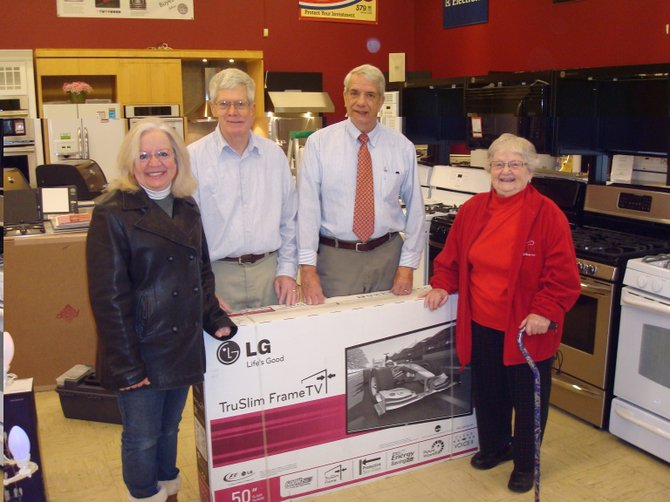 Cazenovia Lion Pam Kent, left, stands beside Larry Aller of Buyea's True Value and Cazenovia Lions Club President Doug Taber as they present raffle winner Joan Mckissick with her new television.