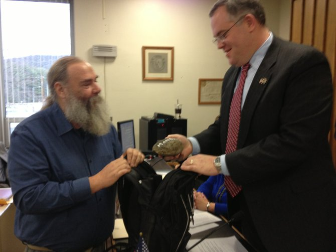 Assemblyman-Elect Dan Stec pulls one of several rocks out of a backpack presented to him Dec. 21 by Johnsburgh Supervisor Ron Vanselow (left) and Hague Supervisor Edna Frasier.  The gag gift represented Stec's oft-repeated metaphor of how the state passes off its burdens to the struggling local municipalities , without providing funding.