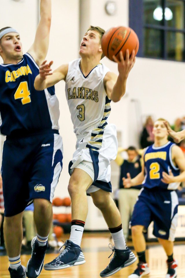 Skaneateles guard Alex Brownlee (3) goes up for a shot, closely guarded by Cazenovia's Jeff Dewan (4), in last Friday's game, won by Skaneateles 52-40.