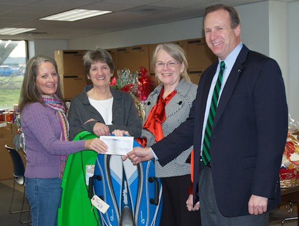 Outreach Coordinators, from left, Jacque McConnaghy and Pat Snyder accept a check from Rotarians Judith Pastel (also interim superintendent of schools) and Peter Adams (Rotary Club President).