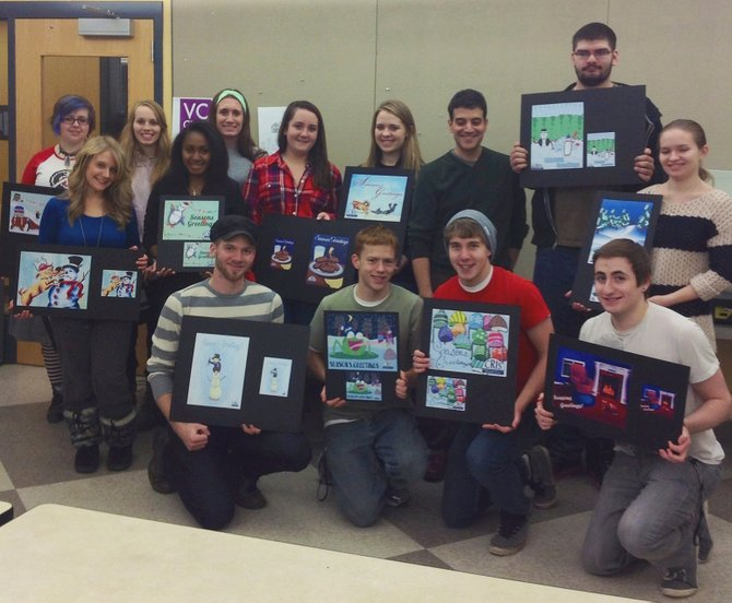 Dan Salamida's illustration students showing their card designs. In the back row stand Meghan Wicklow, left, Natalli Bogart and Samantha King. In the middle row are Amy Plocharczyk, left, Amber Lenon, Angela Martini, Katie McCutcheon, instructor Dan Salamida, Anthony Tedesco and Mackenzie Huba. In front kneel Kyle Robinson, left, Pat Ormsby, Paul Roberts and Macklin Heishman. Not pictured: Courtenay Chambers, Jessica Lacelle, Lisa Hoffman.