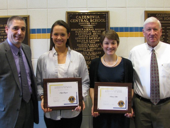 Cazenovia High School Principal Eric Schnabl, left, stands with students Sally Langan and Rebecca Pfohl after Cazenovia Lions Club member Steve Burrell presented them with Student of the Month plaques.