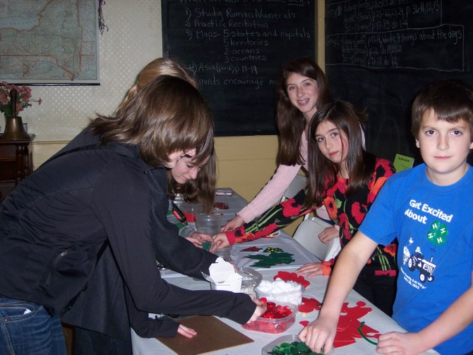 Members of the Lincklaen Shamrocks, a 4-H group from Cazenovia, assist other young local residents in creating holiday crafts on Dec. 9 in the Rippleton Schoolhouse, during Christmas at Lorenzo festivities.