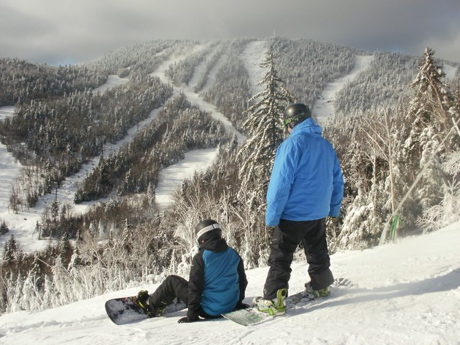 Two snowboarders enjoy the view at Gore Mountain ski center from Bear Mountains Uncas Trail on Christmas Eve.