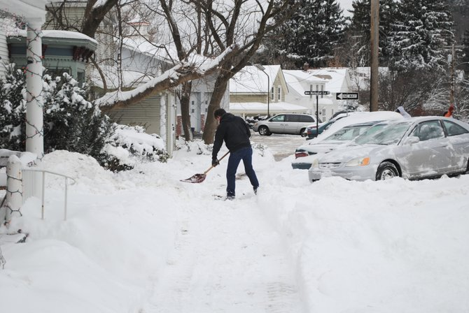 A man in downtown Middlebury shovels snow that fell between Dec. 28 and Dec. 30.