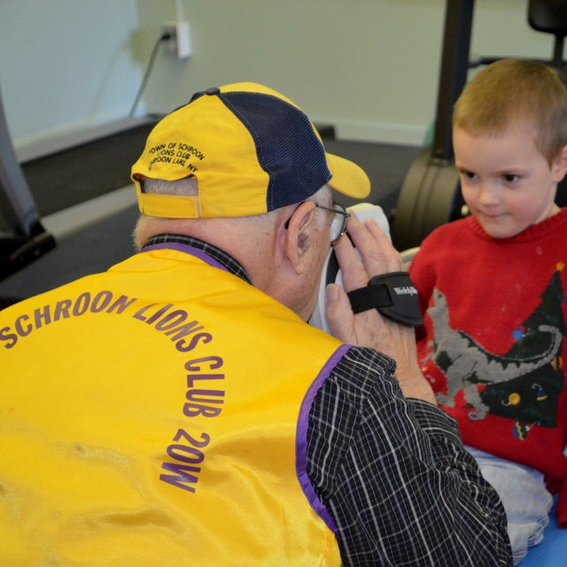 Schroon Lion Dick Newell scans a young man's eyes as part of the Lions SEE program. The program has visited Schroon Lake and Crown Point schools.