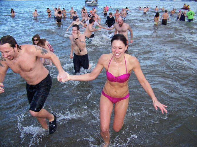 A couple runs for their warm clothing after swimming for several minutes Tuesday Jan. 1 in Lake George annual New Year's Day  Polar Plunge.  Braving bitter cold and gusty wind, more than 1,000 people in swimming suits, shorts, bikinis — and some in bizarre costumes — charged into the frigid waters in the time-honored ritual.
