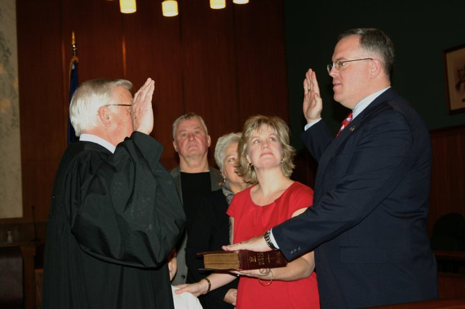 New state Assemblyman Dan Stec (right) recites his oath of office, administered by state Supreme Court Justice David Krogmann (left) while Stec's wife Hilary (center right) watches history in the making on Jan. 1. Stec's parents, George and Elsie Stec (background), witness the ceremony.