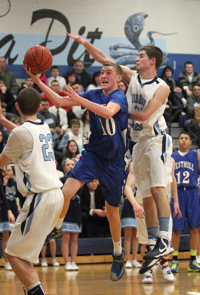 Westhill forward Dan O'Connell (21) drives to the basket, in between Bishop Grimes' Tom Steinberg (23) and Ryan Gosson, in Friday night's game, where the Warriors beat the Cobras 55-44.