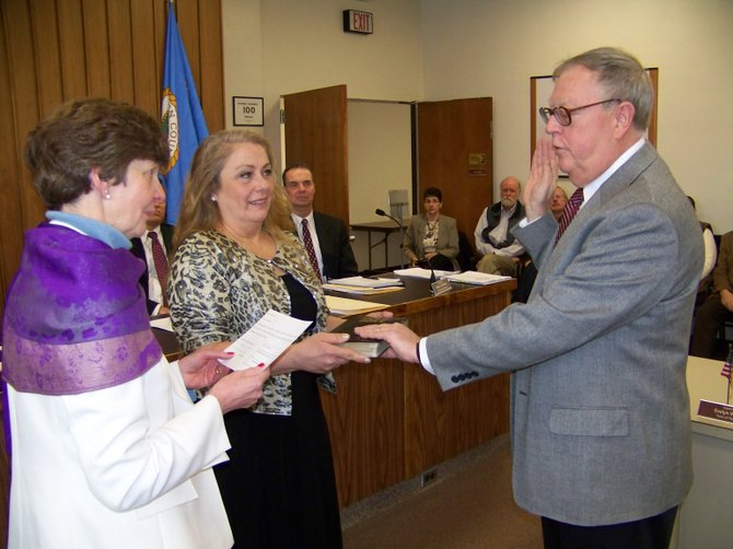 Kevin Geraghty of Warrensburg is sworn in Friday Jan. 4 as he becomes Warren County's new Chairman of the Board of Supervisors. County Clerk Pam Vogel (left) administers the oath of office as Geraghty's wife Kathleen observes the ceremony. Geraghty is the first Warrensburg resident to lead the county in 51 years.