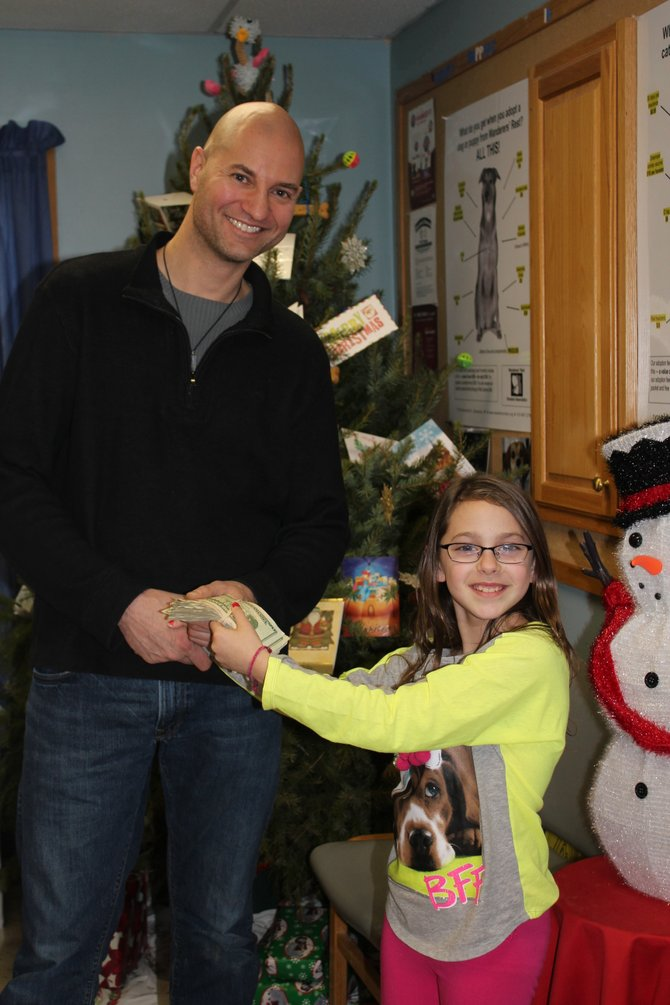 Cazenovia resident Helena Bonavita hands over $225 she raised selling her original artwork to Wanderers Rest Humane Association Executive Director Mark Christensen on Friday, Dec. 21, 2012.