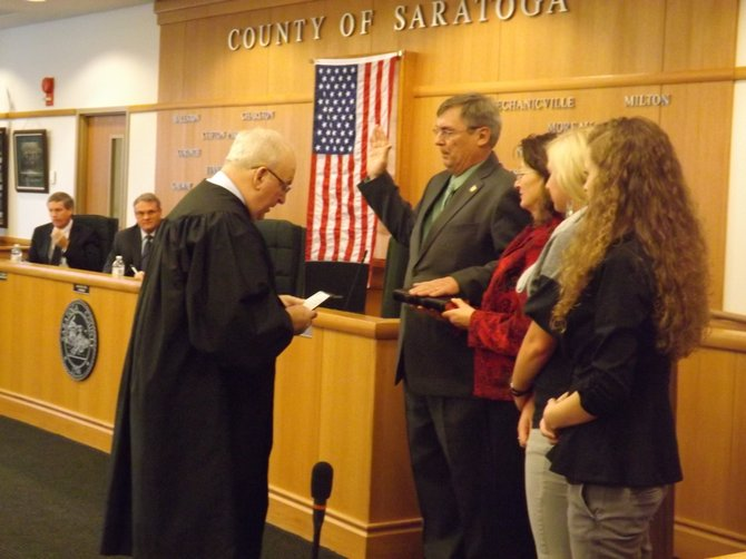 Alan Grattidge is sworn in by former Charlton Supervisor Fred Acunto with his wife Charlotte and two daughters, Emily and Erika looking on.