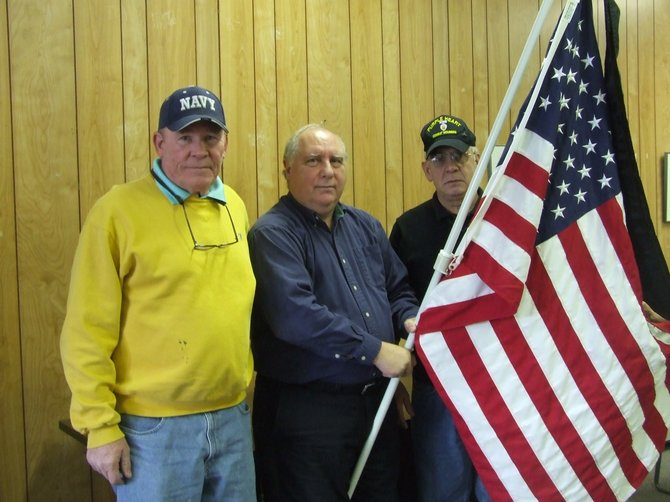 Tom Regan, Gene Loparco and Joe Pollicino stand with one of the mourning flags they hope to place in the Town of Colonie for Memorial Day.