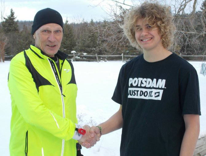 Jim Cunningham, left, treasurer of the LaChute Road Runners Club, congratulates Ben Karkoski on receiving the $1,000 Duane Crammond Memorial Scholarship.
