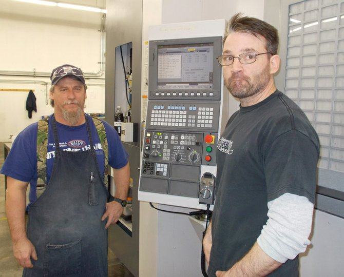 Jim Martin, left, and Eric Moquin stand with a $500,000 horizontal mill at Pre-Tech Precision Machining in Mineville. The equipment is used to make aerospace components.
