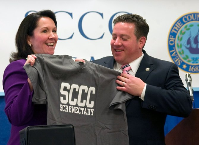 SCCC Board of Trustees Chairwoman Denise Murphy McGraw presents Albany County Executive Dan McCoy with one of the college's T-shirts. College officials on Friday, Jan. 18, announced SCCC would open a satellite campus in downtown Albany.