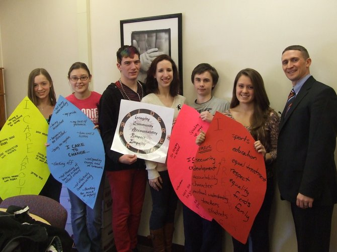 Members of iCARE stand with posters of their core values, including Integrity, Community and Empathy.