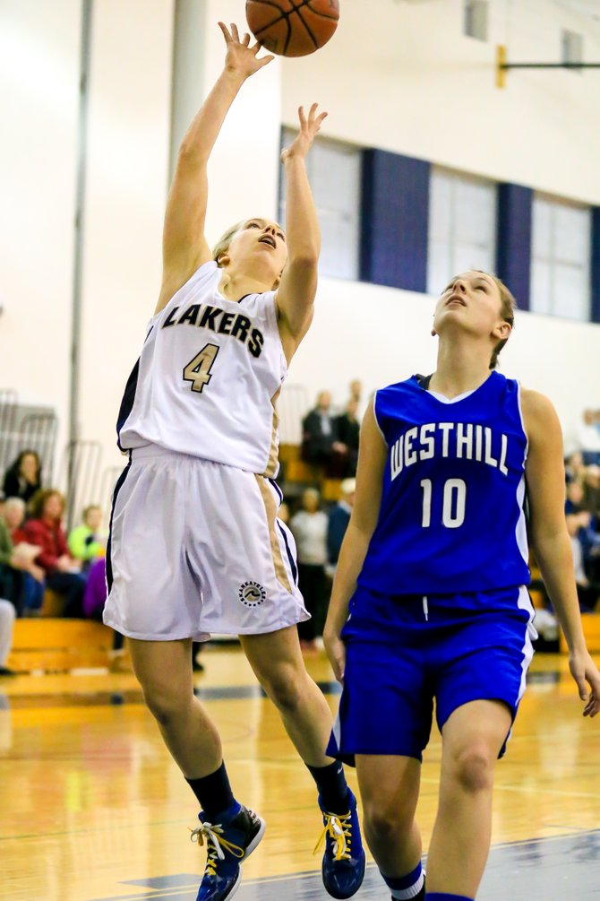 Skaneateles guard Elizabeth Lane (4) drives past Westhill's Maggie Tripodi (10) for a shot in Thursday night's game. Lane had a game-high 19 points, but Tripodi's crucial late 3-pointers helped the Warriors hang on for 54-50 victory to stay undefeated.