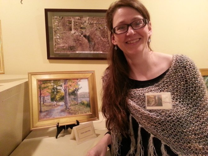 "Jill Dickey poses next to her painting, ""Green Lake"" at a reception at the Manlius Historical Society on Jan. 17."
