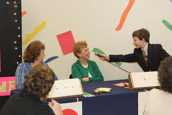 "Woodland Elementary student Jack Walters, right, plays ""Match Game"" host Gene Rayburn from the 60s as he asks Judy Walters a question. East Syracuse Minoa Central School District students hosted ""Games of Life"" for local senior citizens during their third annual intergenerational program."