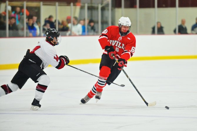 Baldwinsville forward Ronnie Bertrand (6) sidesteps a check by Syracuse's Nate Carr (14) during Thursday night's game. The Bees came from behind to beat the Cougars 4-3.