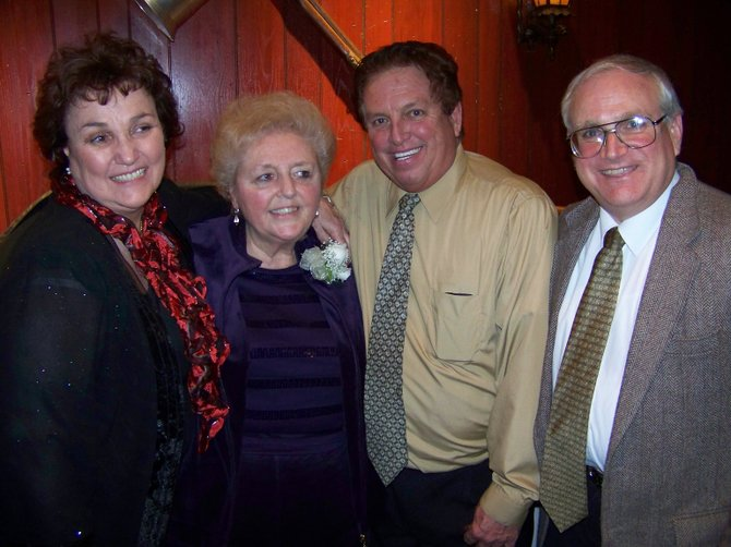 "Sharing a group hug at the Lake george Winter Carnival Friday Feb. 25 while sharing memories of promoter etraordinaire Walt Grishkot, are (left to right): Nancy Nichols, Joan Grishkot, Hal Halliday and Maury Thompson, author of ""The Biggest Kid at the Balloon Festival,"" a biography of Walt Grishkot."