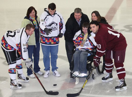 Morrisville Mustangs captain Jamie Nelson (22), left, is joined by Potsdam captain Matt Viola for the ceremonial puck drop. Also joining in the for puck drop were Jeremy Kelley (standing in jersey) and Nelson's cousin Jordan Sykes (in wheelchair), who are both autistic, along with their parents.