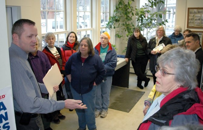 Jeff Sands, left, of the United States Postal Service talks to residents in Essex about changing the hours of operation for their post office.