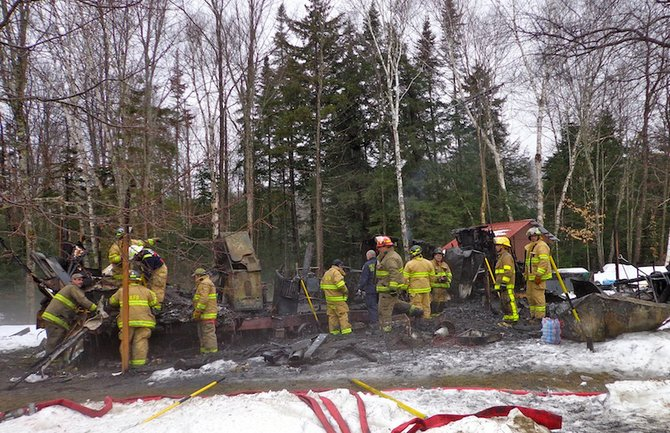 Firefighters look through the scene of a fire that destroyed a mobile home and killed two people in Indian Lake Wednesday, Jan. 30.