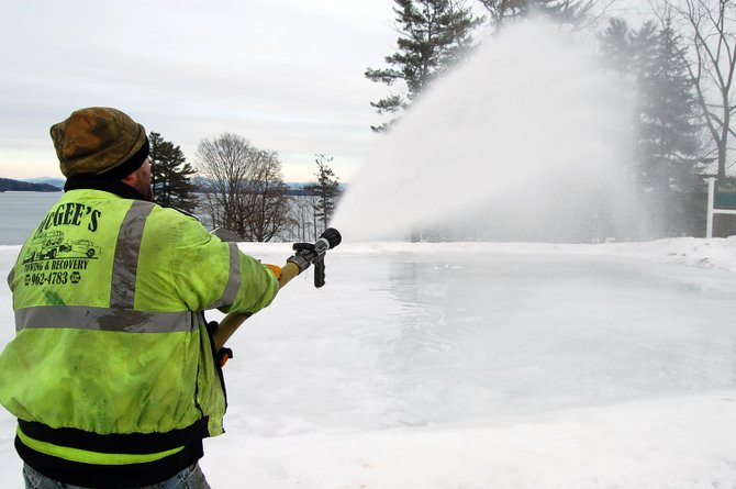 Randy Montville adds water to the Westport outdoor skating rink, located at Ballard Park. Several towns offer skating rinks throughout the region.