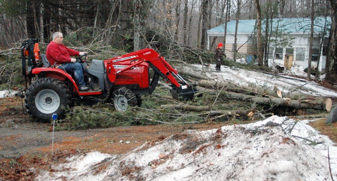 Eric Quain removes downed tree debris from a driveway in Lewis.