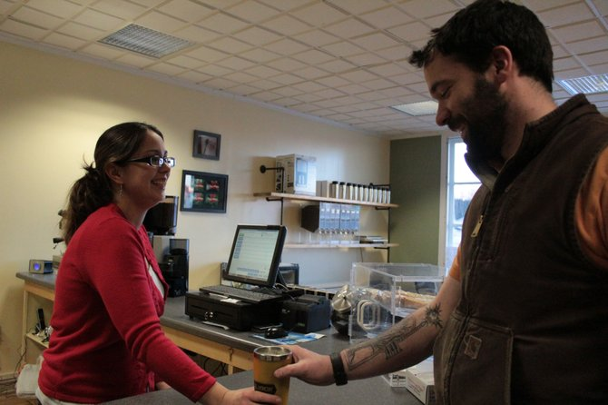 Justin Stearns buys coffee from Crissie Bast of Adirondack Coffee Roasters during their grand opening Monday, Feb. 4.