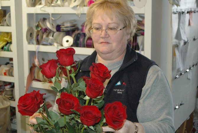 Tracey Sayre prepares a dozen roses for Valentines Day. Sayre has already started to receive advanced orders for Feb. 14.