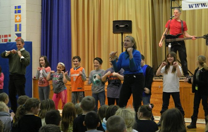 "Susie Rozler, standing front, shows the audience of third and fourth grade students and teachers at Burton Street dance moves as she and Judd Sunshine, on stage, two members of The Hill Brothers, sing their song, ""There's no place for bullies in our school."""