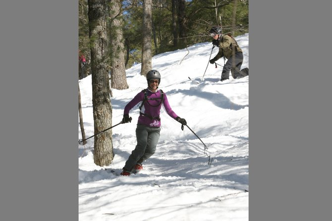 "Two fans of classic downhill skiing enjoy the experience of traveling through ""Paul's Peril,"" one of the glades maintained at Warrensburg's Hickory Ski Center in addition to their open trails and slopes."