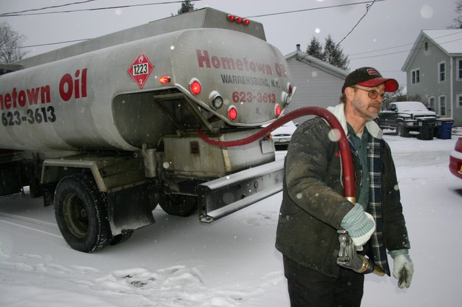 In advance of the weekend's snowstorm, a Hometown Oil employee delivers heating fuel to a household in Warrensburg. With temperatures plunging in recent weeks, concerns have increased in Bolton over those who can't afford the steep price of home heat — and people are being asked to consider donating to the local 'Heat Our Neigbor' program.
