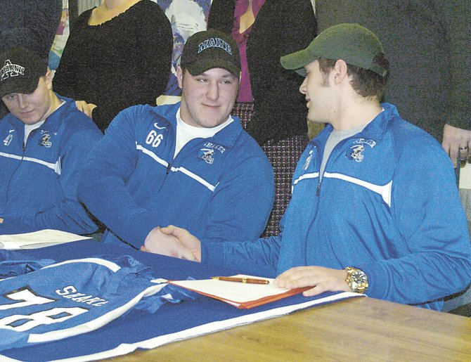 Shaker football players Ryan Griffin, left, Schuyler Huntington, center, and David Morrison sign their National Letters of Intent Feb. 6.