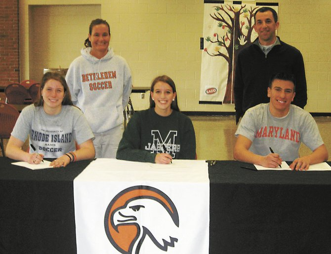 Bethlehem seniors Katie Nickles, left, Tara Teal, middle, and Victor Fox pose with their coaches as each sign a National Letter of Intent to play for their respective colleges Wednesday, Feb. 6. Nickles will attend the University of Rhode Island, Teal will go to Manhattan College and Fox will go to the University of Maryland.