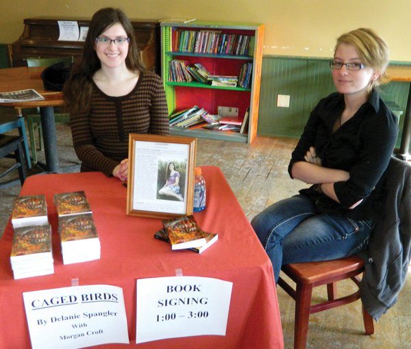 Delanie Spangler, left, and Morgan Croft sit in Common Grounds on Saturday, Feb. 9, for a book signing for their debut novel, &quot;Caged Birds.&quot; The two friends came up with the characters and plot line together and Spangler did the writing.
