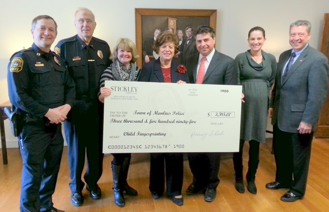 From left: Manlius Police Officer Brian Ackerman, Manlius Police Chief Fran Marlowe, Manlius Town Councilor Karen Greene, Stickley CEO Aminy Audi, Stickley President Edward Audi, Stickley Social Activities Committee Director Jessica Souza, and Manlius Town Supervisor Ed Theobald stand with the check for $3,595.