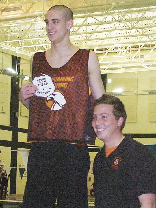 Bethlehem's Gunnar Zemering accepts his 50-yard freestyle championship patch from coach Bill Dergosits at Saturday's Section II Division I meet at the Shenendehowa Aquatic Center.