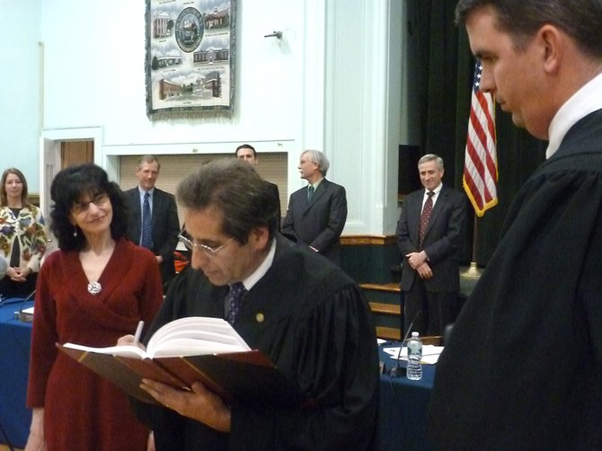 Michael Katzer is sworn in to office by Town Justice Ryan Donovan Feb. 13, with wife Lita Katzer at his side.
