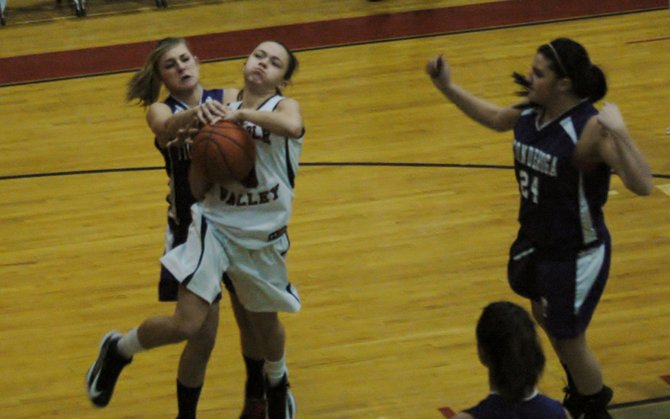 Taylor Saltus of AuSable Valley goes up for a shot against Lesli Moore of Ticonderoga as Meg Campney follows the play