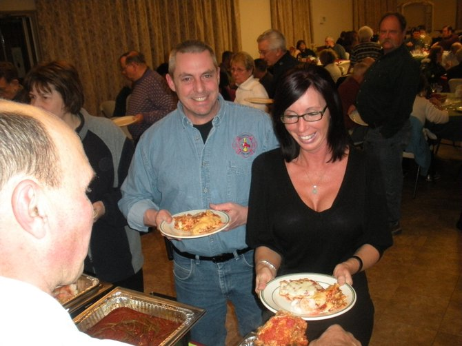 Scott Turner and Kim Pelton are served lasagna by Gary Oliver at the American Legion's Italian Feast Night.