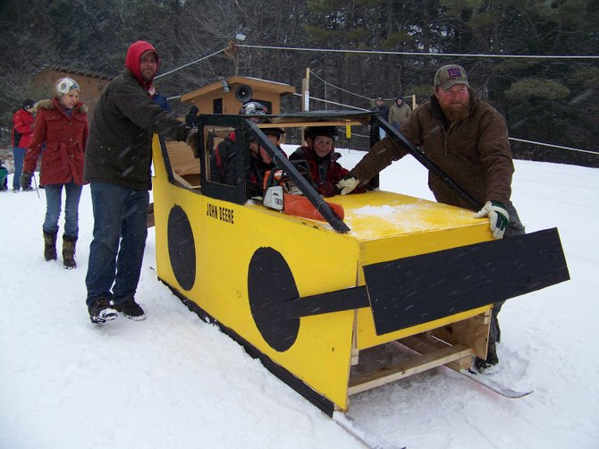 Ready to race downhill in the Krazy Downhill Derby held Saturday Feb. 23 in Chestertown are young Baker siblings Hayden, 4; Cyrus, 5; and Wyatt, 10. Their father Aaron and Sean of Baker logging get ready to launch the bulky craft, fashioned after a John Deere skidder by the Baker family.