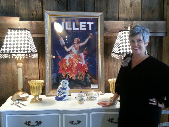 Lisa Hogan stands in front of a dresser she refurbished at Shabby Chic Boutique in Fayetteville.