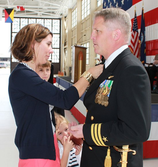 Jeanette Townsend, left, pins the command at sea pin on her husband, Jon Townsend, after he assumed command of Patrol Squadron Six Two on Feb. 23 in Jacksonville, Fla.