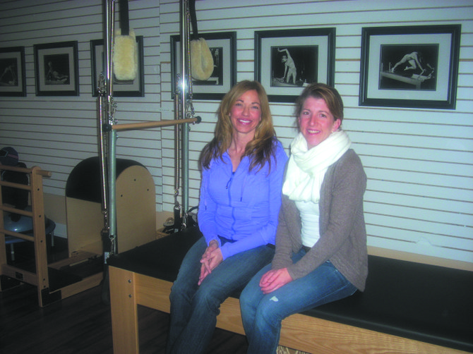 """Arlene Reiss (left) and Deb Bobbett (right) the co-owners of Well Balanced Studio at 22 Jordan St., sit on the """"Cadillac,"""" a piece of equipment used for Pilates, in their newly opened studio."""