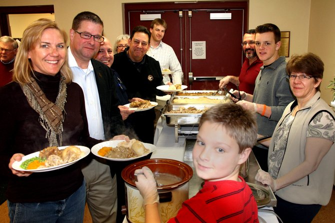Alex Duggleby, 9, Karen Fitzgibbons, Nate Olson, 16 and Matt Fitzgibbons serve food to hungry guests