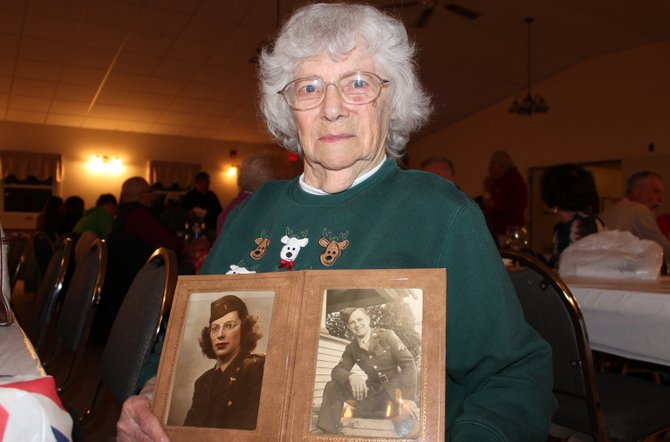 Dorothy LeClair, an Army Nurse during World War II, holding a photo of herself, left, and her husband, Carl LeClair, who served in the Army during World War II.